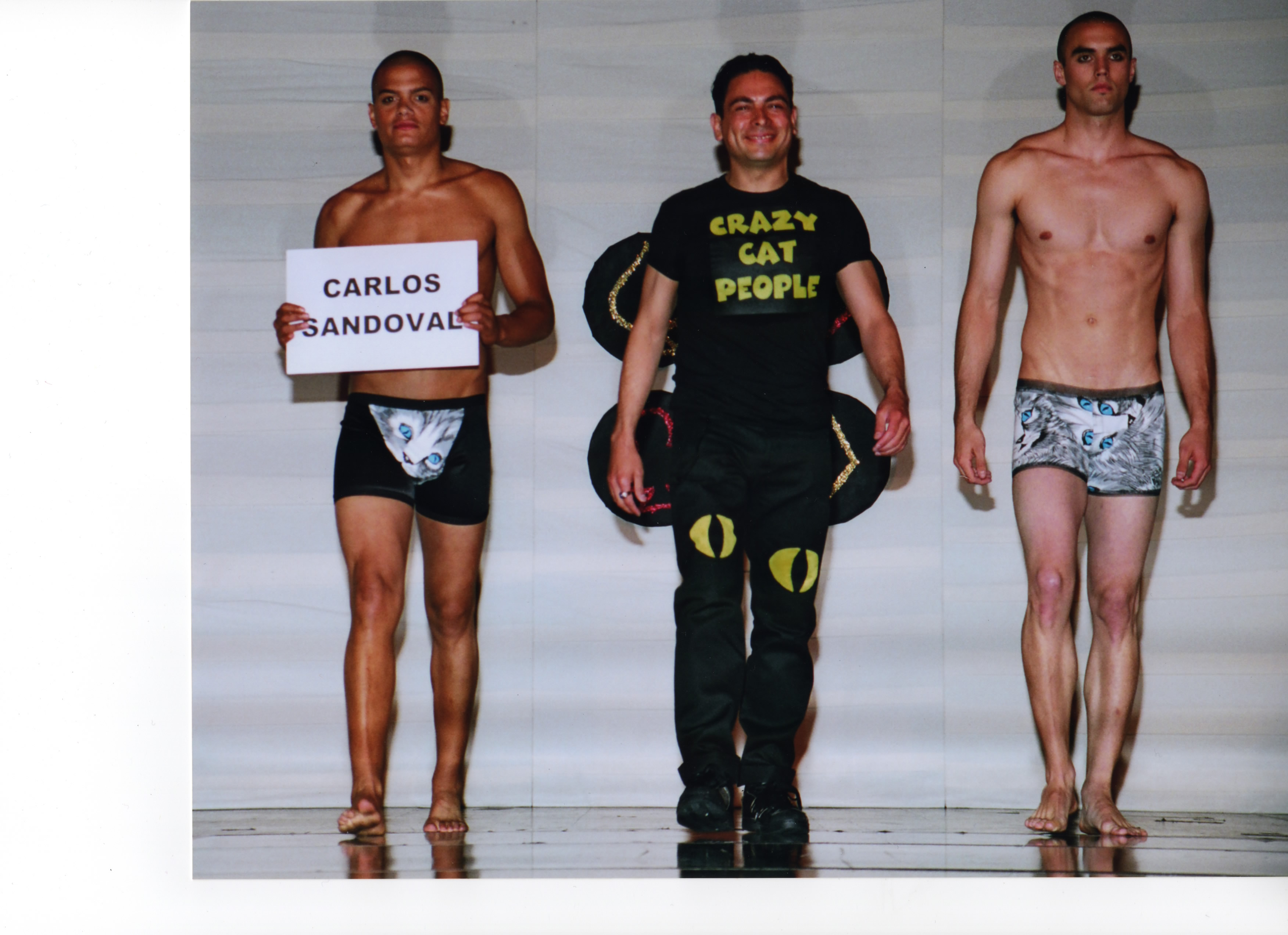 Fashion designer Carlos Sandoval wearing a Crazy Cat People shirt with cat eyes on the pant legs. On each side is a male model wearing cat-themed swimwear