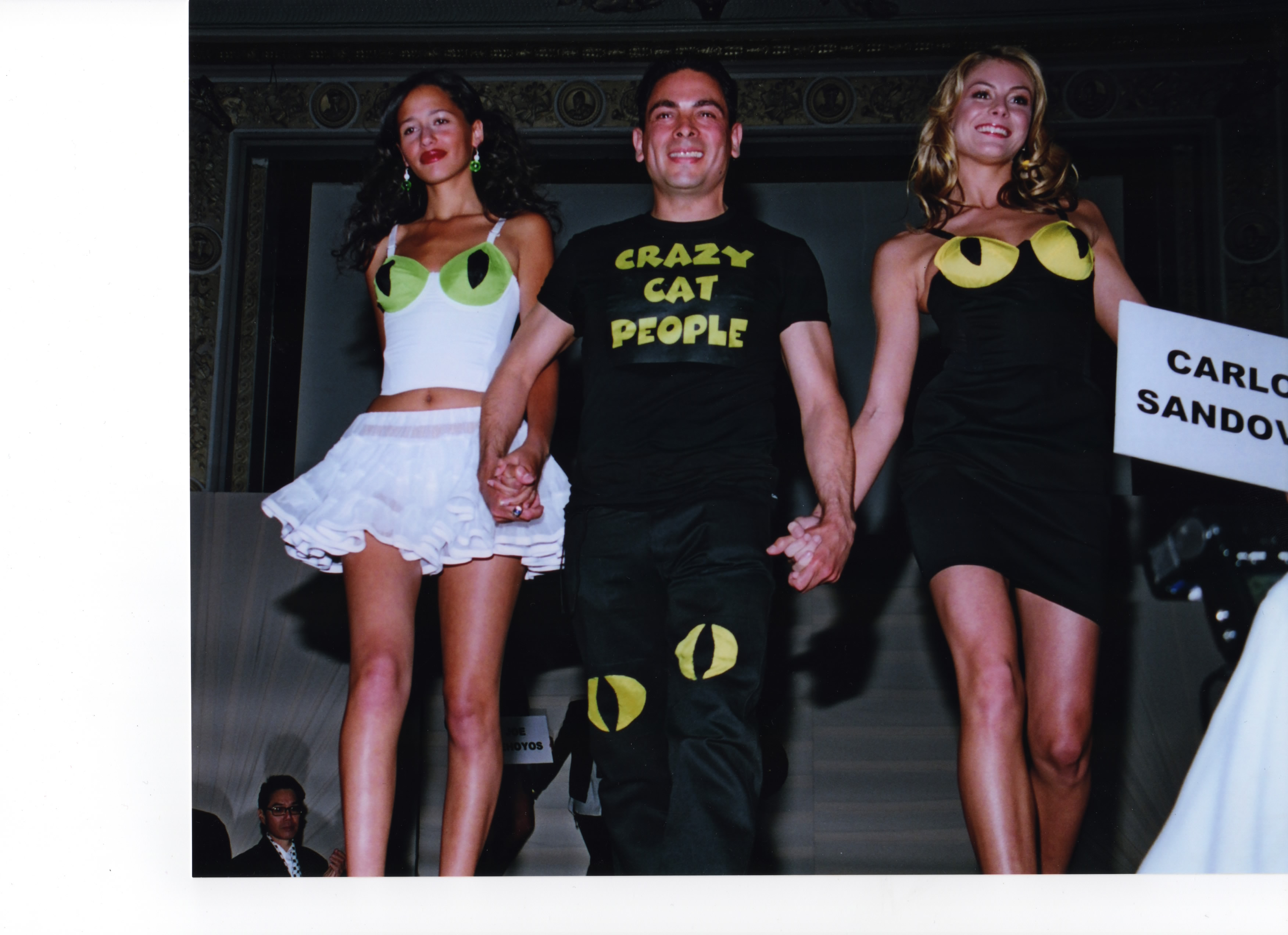 Illustrator Carlos Sandoval with two models wearing crazy cat people dresses