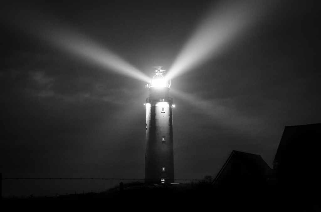 lighthouse with rays of light in the darkness
